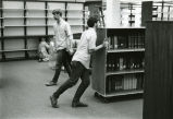 Male students shifting books in Nyselius Library, Reference Section