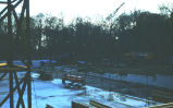 Concrete foundation and equipment on the construction site of Alumni Hall at dusk looking...